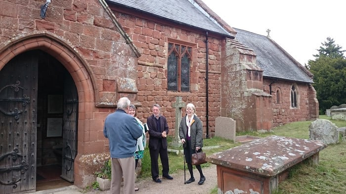 Several people chatting at the entrance to Ruyton Church